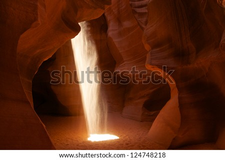 A beam of light shines down through the walls of Upper Antelope Canyon near Page, Arizona. - stock photo
