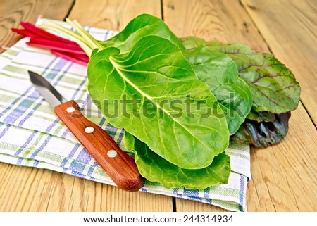A beam of red and yellow chard with a knife on a napkin on a wooden boards background - stock photo