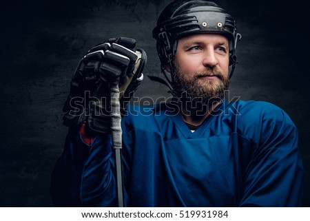 A bearded ice-hockey player in a blue sportswear holds a gaming stick in contrast illumination on grey vignette background.