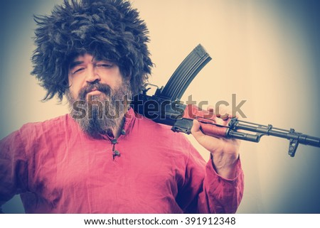 A bearded man in a fur hat and a red shirt holding a gun on his shoulders against the background of a concrete wall. Toned