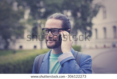 A bearded man in a jacket and sunglasses talking on the phone