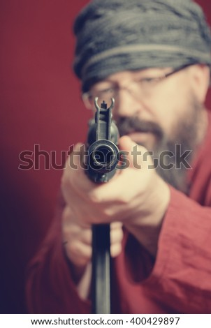 A bearded man in a red shirt, a turban and glasses aiming a gun on a red background