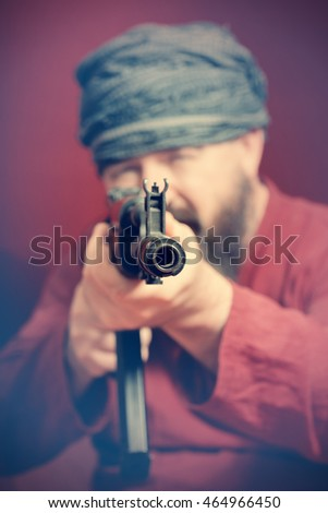 A bearded man in a red shirt and a turban aiming a gun on a red background. Toned