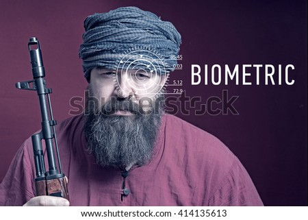 A bearded man in a red shirt and a turban with a weapon and with lines from a facial recognition software and inscription biometric. Toned