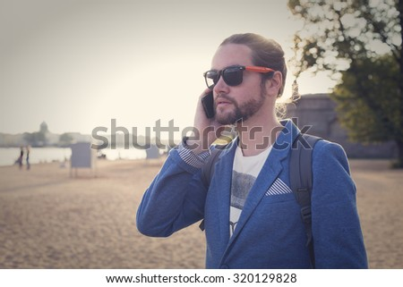 A bearded man in sunglasses talking on cell phone. - stock photo