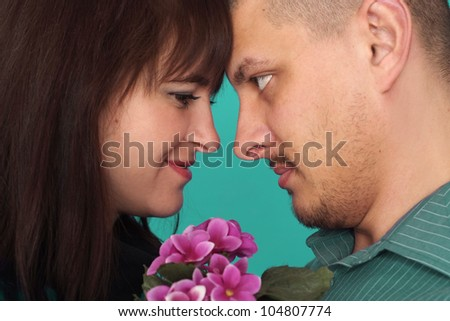 A beautiful adult Caucasian couple with flowers on a blue background