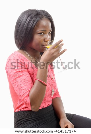 a beautiful African woman drinking orange juice isolated on white background