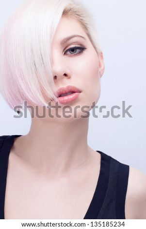 A beautiful and blond scandinavian young woman with creative hair style. Toned and natural retouched. - stock photo