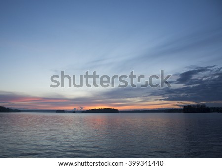 A beautiful and colorful sunset by the lake in Finland. Some clouds are in the blue sky with colorful tones from the sun going down. - stock photo
