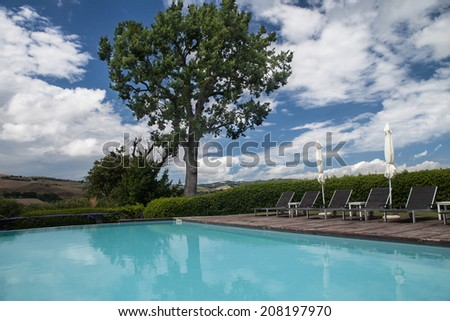 a beautiful and luxurious tuscany swimming pool with parasols and chairs - stock photo
