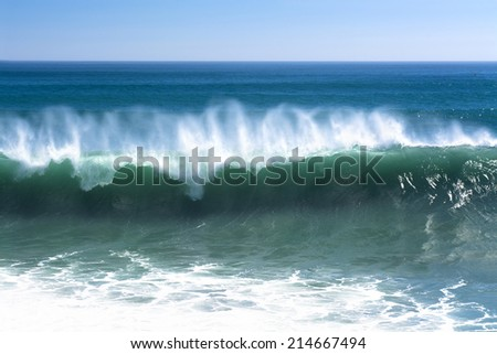 A beautiful and powerful turquoise wave in high winds curls while white spray mist forms and at its crest in Huntington Beach. - stock photo