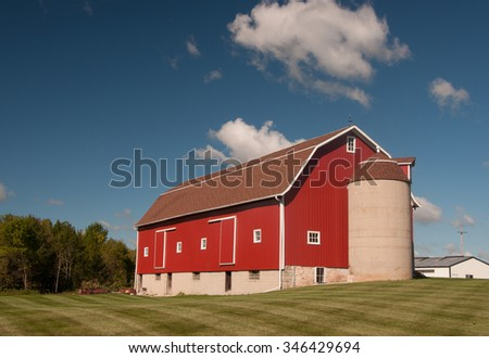 A beautiful and well maintained red barn in an equally well maintained farmyard in Wisconsin.