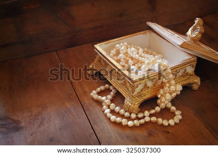 A beautiful antique golden jewelry box with natural white pearls on wooden table. retro filtered image  - stock photo
