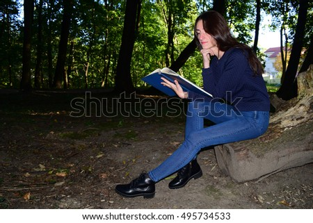 A beautiful Armenia girl is reading a book in Russian forest