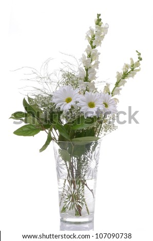 A Beautiful Arrangement of White Flowers in a Crystal Vase on White - stock photo