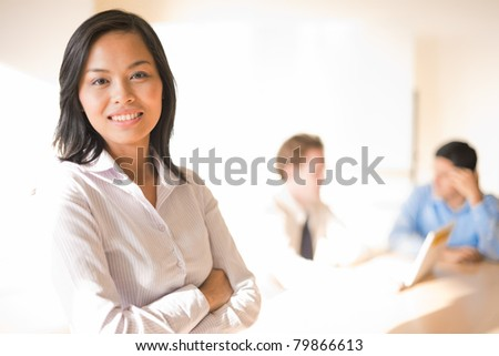 A beautiful asian businesswoman smiling in front of her working colleagues - stock photo