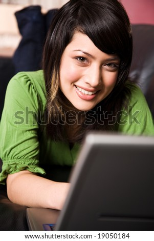A beautiful asian girl relaxing on the sofa working on the laptop