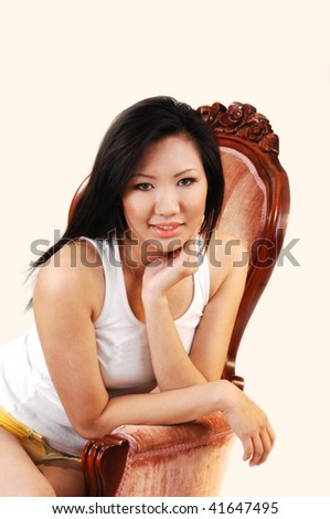 A beautiful Asian woman in an white t-shirt and nice long black hair sitting in a pink armchair.