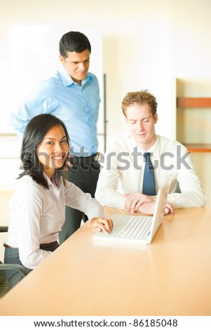 A beautiful Asian woman sitting in white blouse head turned, looking at camera leading a business meeting at conference room table with her male colleagues working together in show of teamwork
