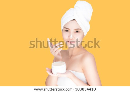 A beautiful asian woman using a skin care product, moisturizer or lotion. isolated with clipping path - stock photo