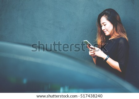 A beautiful asian woman using smart phone with feeling happy and smiley face , standing in front of black concrete wall background