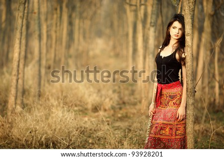 A beautiful autumn girl posing in the forest wearing a red skirt. - stock photo
