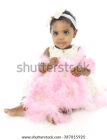 A beautiful baby girl all dressed up in white covered with a pink boa.  On a white background.