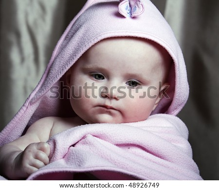 a beautiful baby girl in a pink snuggle robe