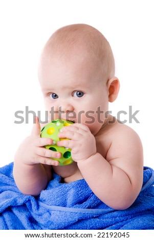 A beautiful  baby wrapped in a blue towel biting green ball