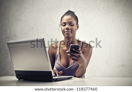A beautiful black woman is smiling while is using a smart-phone and a laptop computer - stock photo