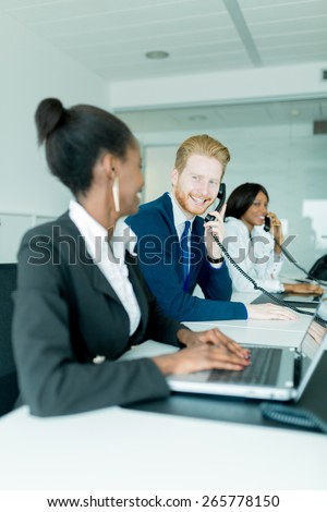 A beautiful, black, young woman working at a call center in an office with her red haired colleague talking to a customer