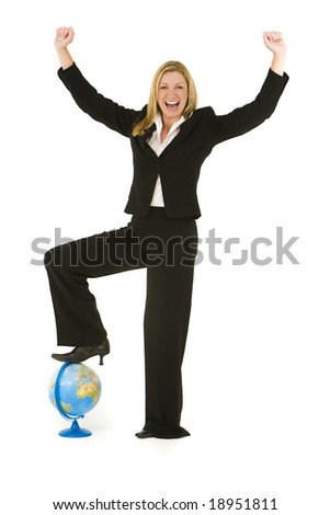 A beautiful blond businesswoman stands with her foot on a globe and raising her arms in conquering celebration