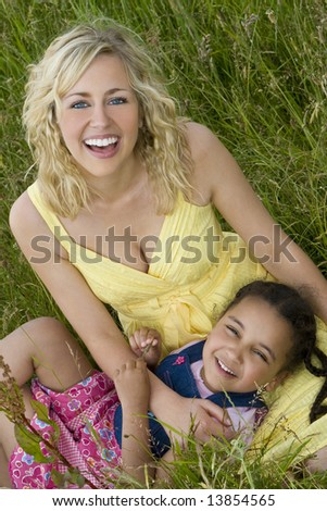 A beautiful blond haired blue eyed young woman having fun with a mixed race young girl in a field of long grass