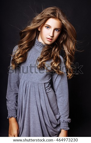 A beautiful blond-haired 13-years old girl in studio on black background