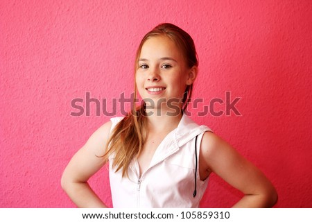 A beautiful blond-haired 13-years old girl, portrait over pink background - stock photo