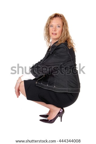 A beautiful blond woman crouching on the floor in a black skirt and navyjacket, isolated for white background. - stock photo