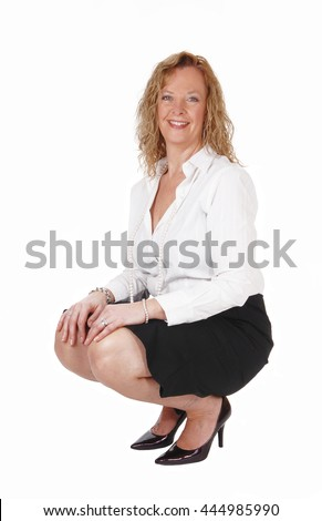 A beautiful blond woman crouching on the floor in a black skirt and whiteblouse, isolated for white background. - stock photo