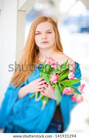 A beautiful blond woman holding a bouquet of flowers. Winter landscape. Snow and wind.