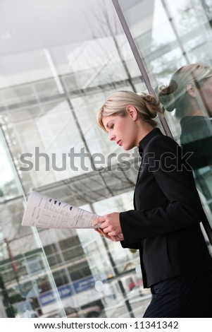 A beautiful blonde business woman reading newspaper