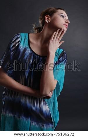 A beautiful blonde girl posing in a studio wearing a black undershirt. - stock photo