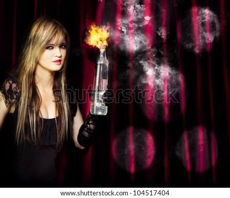 A beautiful blonde hoodlum captured in the act of arson as she holds a burning petrol bomb in her gloved hand intent on setting the theatre on fire conceptual of being caught in the act - stock photo