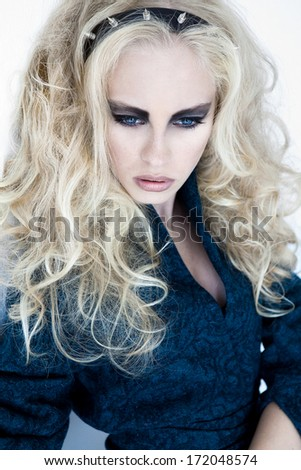 A beautiful blonde is posing a blue coat