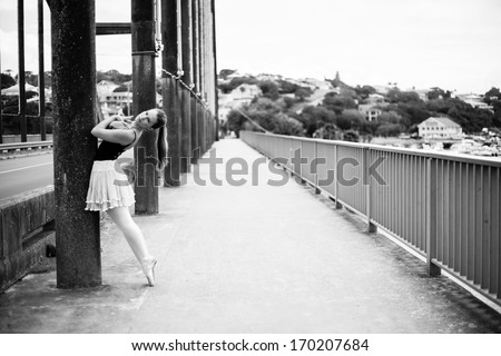 A beautiful blonde lady is standing on top of a bridge leaning against one of the pillars. It isa  black and white photo. - stock photo