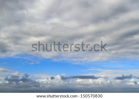 A beautiful blue sky with two layers of clouds is captured on a sunny day. - stock photo