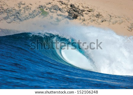 A beautiful blue wave breaks across a reef in rural Mozambique. - stock photo