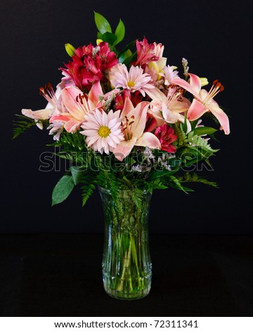 A beautiful bouquet of pink and red lilies, daisies and freesias, with greenery, in a clear glass vase, on a black background
