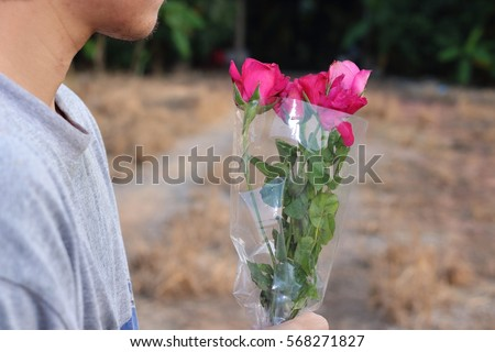 A beautiful bouquet of red roses is held on hand of young relaxed man on nature outdoor background. Love and romance Valentine's day concept.