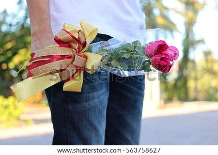 A beautiful bouquet of red roses with ribbon is held by young man with white shirt on nature blurred background. lover and dating concept or Valentine's day