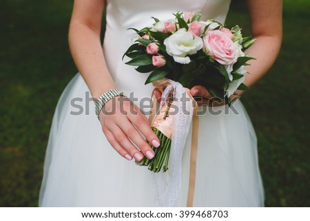 A beautiful bouquet tied with silk ribbons and lace with the key. Wedding bouquet in hands of bride. Wedding Accessories