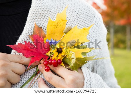 A beautiful  boutonniere made from autumn leaves on a lapel of women's blouse